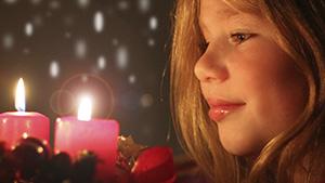 Mädchen betrachtet Adventskranz